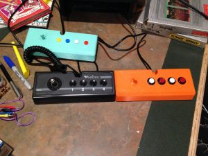 "Early teal version with ""clicky"" buttons, original Vectrex controller in black, and the latest in orange with Sanwa buttons."